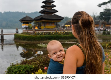 Mom and a baby in Pura Ulun Danu Batur temple, Bali, Indonesia