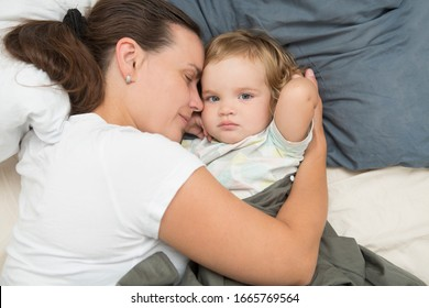 mom with baby relaxing lying on bed at home