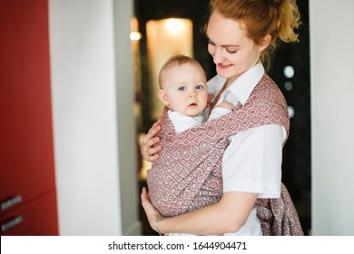 Mom and baby in sling, caring blonde mom gently hugs and plays with her baby son, Sling wear and natural parenthood