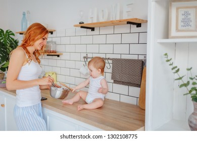 Mom with baby son prepares breakfast / Housewife prepares food / copy space