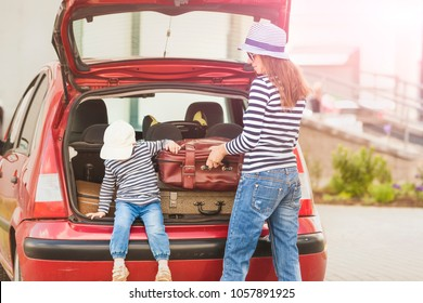 Mom and baby son put the red car suitcases for travel