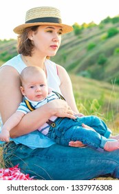 Mom with baby spending time together at sunset, on summer or autumn day, warm sunlight