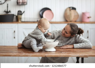 Mom and baby together in a cozy interior in the kitchen, emotions and motherhood, a single mom plays with the baby merrily. Mother's day