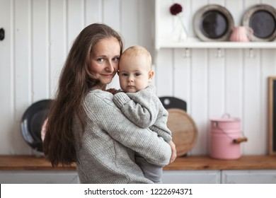 Mom and baby together in gray knitted sweaters in the real kitchen in the interior, the concept of maternal love and interaction with her son.