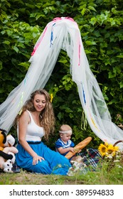Mom with a beautiful little daughter in the summer in nature with decorations and soft toys, a picnic