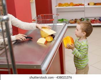 Mom and boy playing in the shop. role-playing. small child playing in the supermarket to buy food. smiling woman behind the counter helps the boy to make a purchase