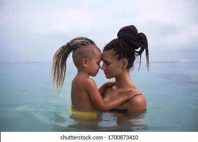 Mom with a boy swimming in the sea, in swimsuits. Dreadlocks on the head. A strapless t-shirt.