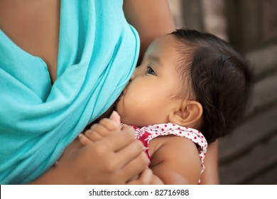 mom breast feeding her baby girl and holding her hand