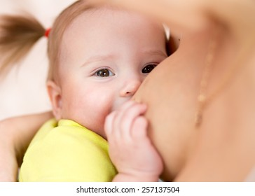 mom breastfeeding baby girl with breast milk