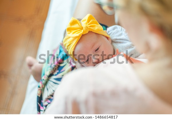 Mom breastfeeding baby girl on bed