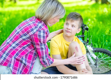 Mom calming her son, who fell while riding a bicycle and scraped his knee