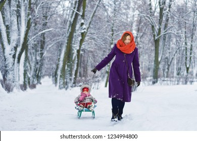 Mom carries a child on a sled in the park in winter