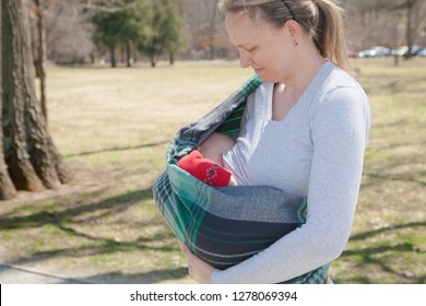 Mom carrying a baby in a sling out for a walk at the park. The baby is breastfeeding.