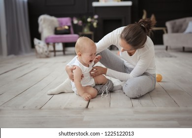 Mom changes clothes crying Baby of 10 months on the floor in a cozy real light interior.