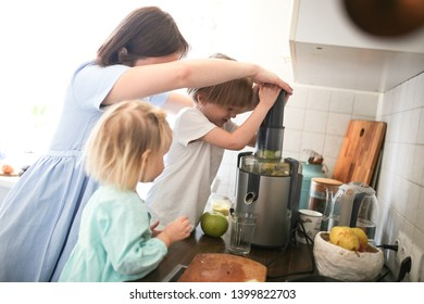 Mom and charming Toddler girl with brother cut apples and squeeze juice in a juicer, brother and sister with a mother with a juicer in a bright interior, lifestyle