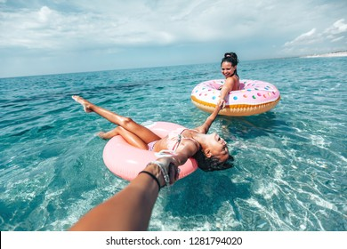 Mom with child chilling on lilo in the sea water. Family relaxing on inflatable rings on the beach. Summer vacations, idyllic scene.