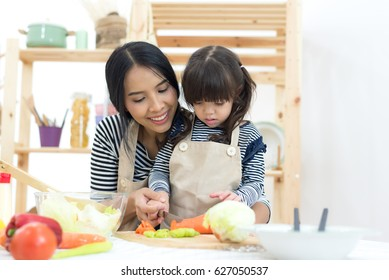 Mom and Child cooking and cutting vegetables on kitchen