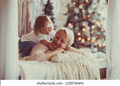 mom and a child with down syndrome cuddling together on a bed against the backdrop of a new year's Christmas tree, concept holidays, new year and xmas in the family