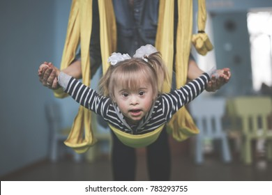 Mom with child Down syndrome engaged in sport, a yellow hammock and a children's center,  concept childhood, lifestyle and toning