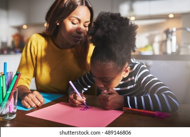 Mom and child drawing in kitchen, black mother and daughter