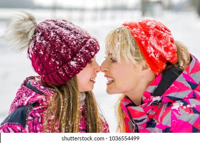 Mom and child girl kiss with noses on snowy winter day in park. Profile of mother and daughter face to face. Snow flakes on winter pink clothes. Happy family.