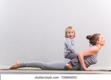 Mom and child  hatha yoga in a cobra pose
