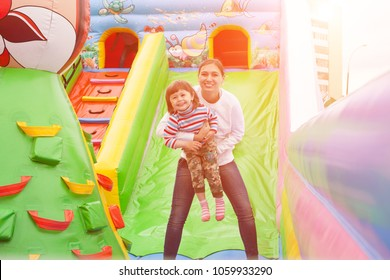 Mom and child jumping in an inflatable castle