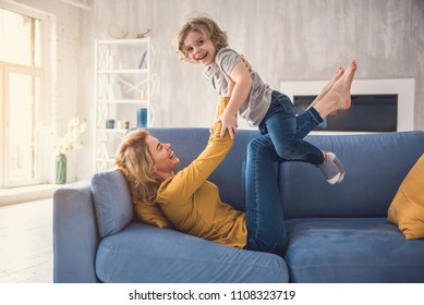 Mom and child are laughing on divan while spending time together. Woman is swinging and raising kid on her legs while lying on couch. Boy is holding parent arms and looking at camera with excitement