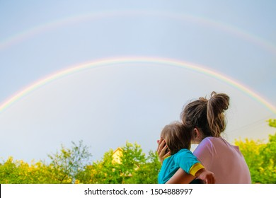 Mom with a child looks at the rainbow. Mom and son on the background of motherhood. Look at the rainbow.