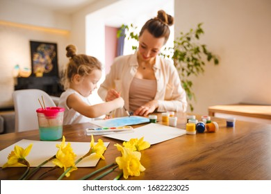Mom with a child paint in the kitchen.