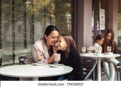 Mom with child spending time in outdoor cafe. Mother with her daughter talking and drinking cocoa for the breakfast in the city street in autumn. Urban family weekend.