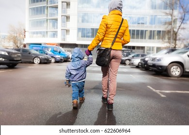 Mom and child are walking along the parking lot to the store