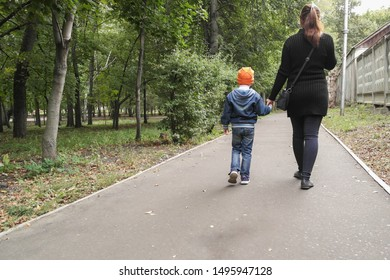 Mom and child walking on the asphalt path in the Park. Rear view - a woman and a boy holding hands and walking along the plantings. Family outdoors in early autumn. Walk through ecological areas.