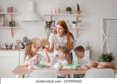 Mom and children are sitting at the table in the kitchen