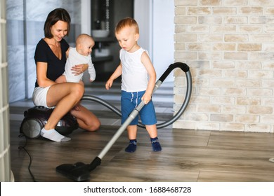 Mom with children vacuums the floor, children ride on a vacuum cleaner, quarantine and household chores at home.