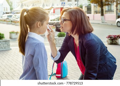 Mom comforting her crying daughter schoolgirl on the way home from school - the concept of parenthood
