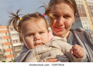 Mom with a cute daughter swinging on a swing at sunset