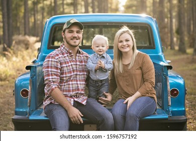 mom, dad and baby toddler son family sitting on a vintage blue pick-up truck bed and the little one is clapping