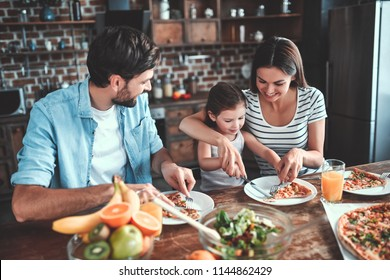 Mom, dad and daughter are eating together on kitchen. Happy family concept.