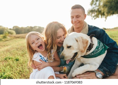 Mom, dad, and daughter having fun playing with big dog in the garden at sunset