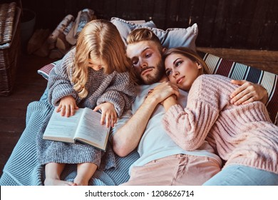 Mom, dad and daughter reading storybook together while lying on bed.