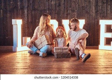 Mom, dad and daughter sits together with gifts in room decorated with voluminous letters with illumination.