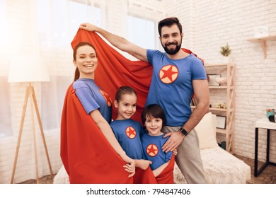 Mom, dad, daughter and son in suits of superheroes are posing for a camera in their apartment. They have a happy family.