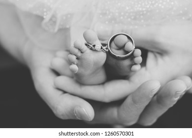 Mom and dad hands holding a newborn baby with wedding rings on the feet of the child.