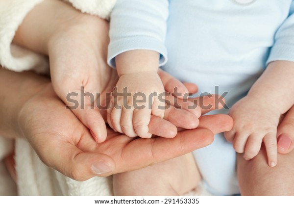 Mom and Dad hold baby's hand