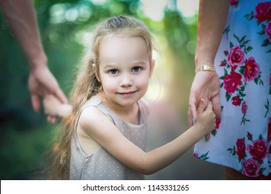 Mom and dad hold their daughter hands. Happy successful family. Mother's, Children's or Father's Day concept image. Give more time for your kids. Family values