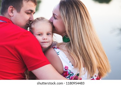 Mom and dad hold their daughter hands. Happy successful family. Mother's Day, Children's or Father's Day concept image. Give more time for your kids. Family values. Happy Society. Success Community