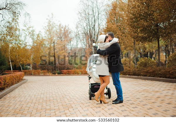 Mom and Dad hugging in the autumn park