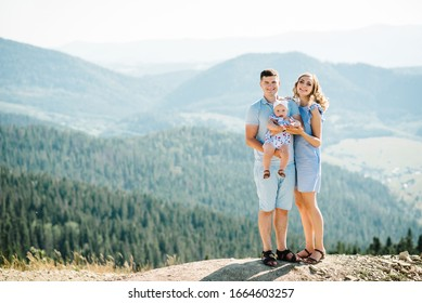 Mom, dad hugging daughter in the mountains enjoy and look at nature. Young family spending time together on vacation, outdoors. The concept of family summer holiday. Mother's, father's, baby's day.