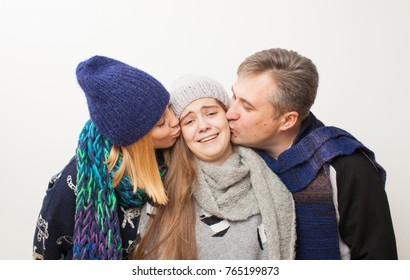Mom, dad kiss poor teen daughter on white background. Family in warm clothes on white background.